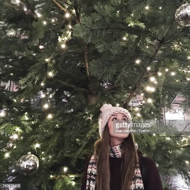 Low Angle View Of Woman Standing By Illuminated Against Christmas Tree