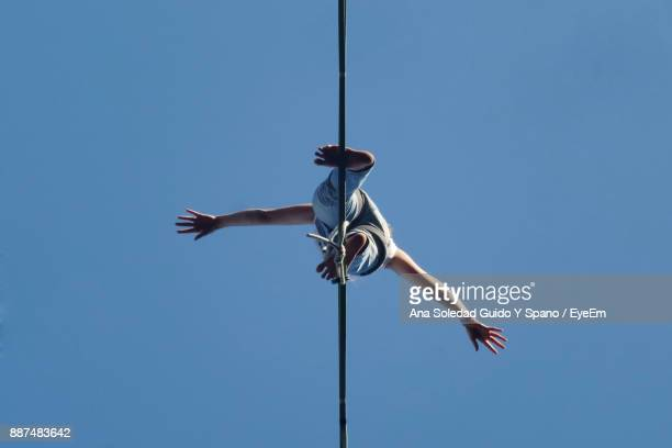 Low Angle View Of Woman Standing Cable Against Clear Sky