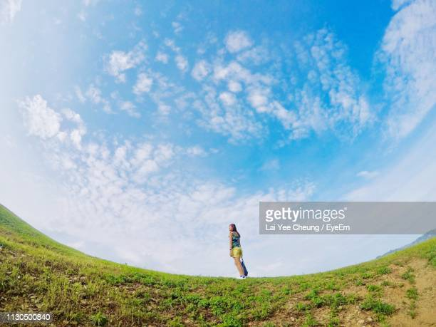 low angle view of woman standing on field against blue sky - grande angular - fotografias e filmes do acervo