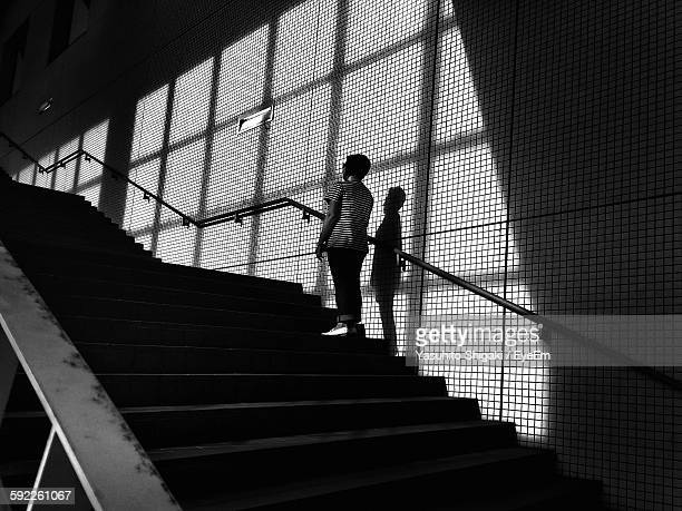 low angle view of woman standing on staircase at tokyo big sight - tokyo big sight stock photos and pictures