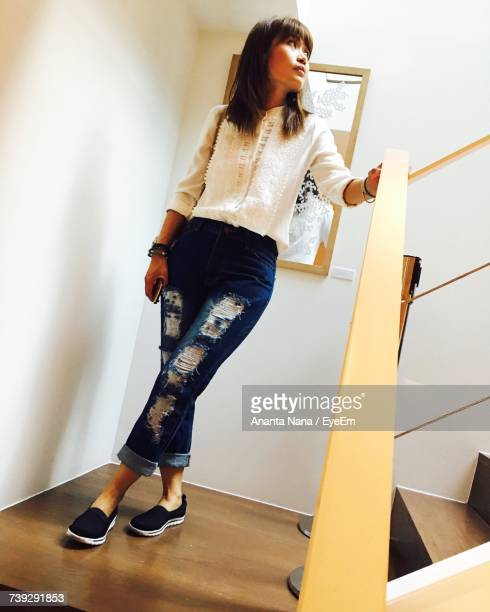 Low Angle View Of Woman Standing On Steps At Home