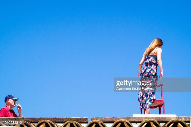 Low Angle View Of Woman Standing On Table By Chair Against Clear Blue Sky