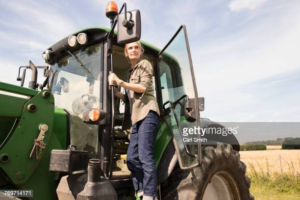 low angle view of woman standing on tractor at farm against sky during sunny day - tractor stock pictures, royalty-free photos & images