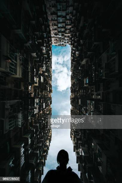 low angle view of woman surrounded by old traditional buildings in city against clear blue sky - skyscraper film stock pictures, royalty-free photos & images