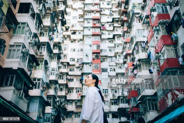 Low angle view of woman surrounded by old traditional residential buildings and looking up to sky in city