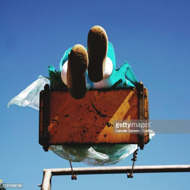 low angle view of woman swinging against clear blue sky - human leg stock pictures, royalty-free photos & images