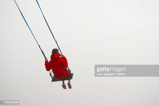 low angle view of woman swinging against cleat sky - swinging stock pictures, royalty-free photos & images