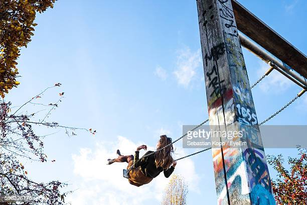 low angle view of woman swinging against sky - freiheit stock-fotos und bilder