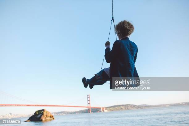 Low Angle View Of Woman Swinging Over Sea Against Sky With Golden Gate Bridge In Background