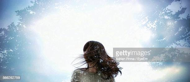 Low Angle View Of Woman Tousled Hair During Snowfall On Sunny Day