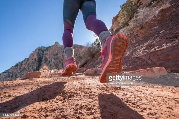 vista ad angolo basso del sentiero femminile che corre in una montagna polverosa nel deserto; persone sport all'aperto concetto - arizona foto e immagini stock
