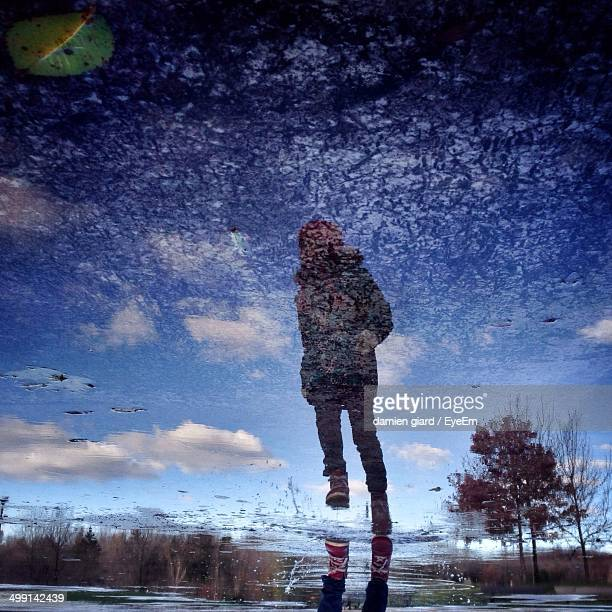 Low angle view of woman walking against blue sky