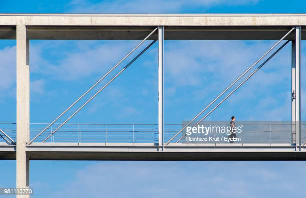 Low Angle View Of Woman Walking On Bridge