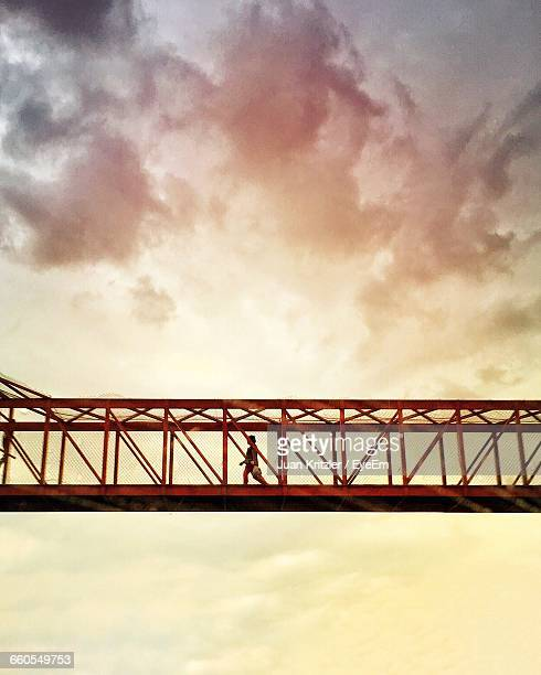 Low Angle View Of Woman Walking On Footbridge At Sunset