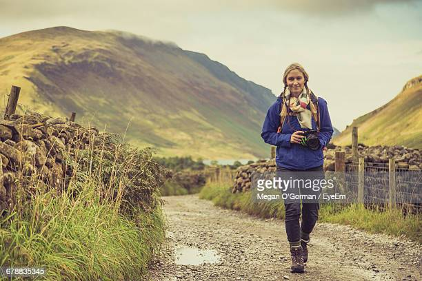 Low Angle View Of Woman Walking On Footpath