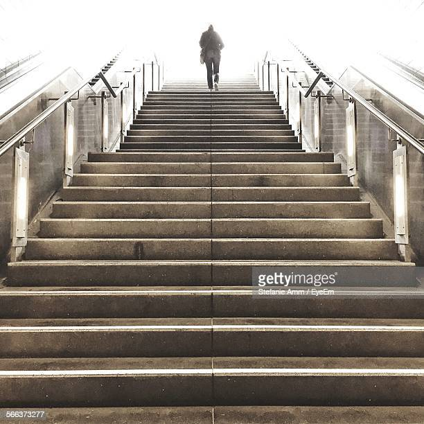 low angle view of woman walking up stairs - stairs stock photos and pictures