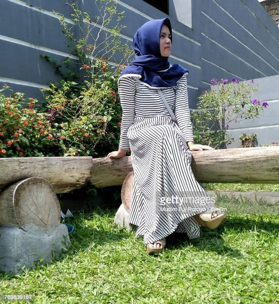 Low Angle View Of Woman Wearing Hijab While Sitting On Bench