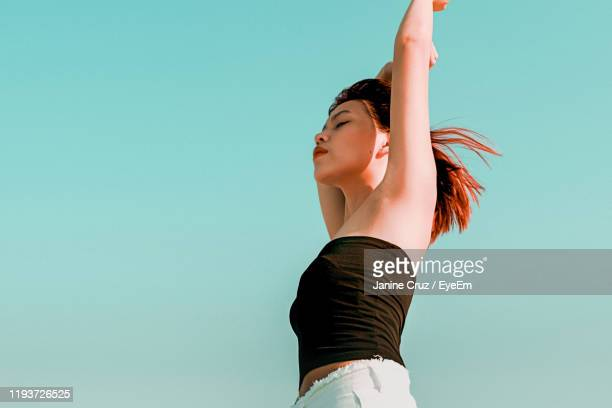 low angle view of woman with arms raised and closed eyes standing against sky - filipino woman stock pictures, royalty-free photos & images