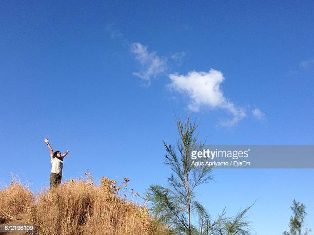 Low Angle View Of Woman With Arms Raised Standing On Hill Against Sky