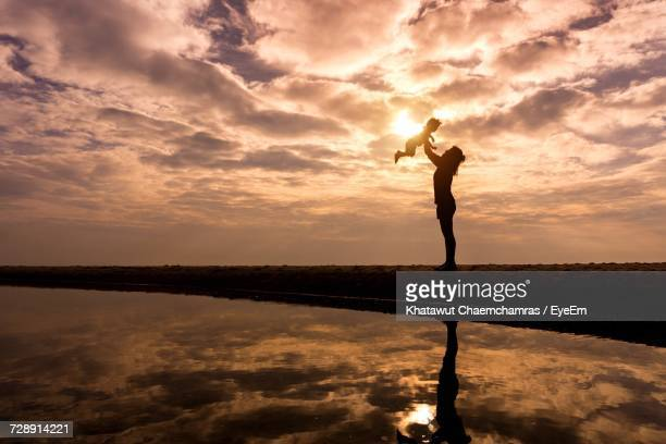 Low Angle View Of Woman With Baby By Lake Against Cloudy Sky During Sunset