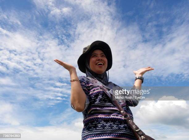 Low Angle View Of Woman With Hands Raised Laughing Against Cloudy Sky