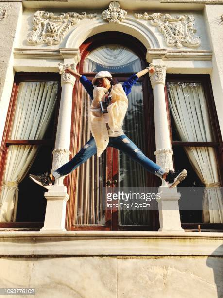 Low Angle View Of Woman With Legs Apart Jumping Against Building