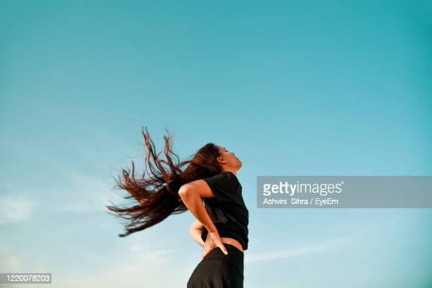 low angle view of woman with long hair standing against clear blue sky - wind stock pictures, royalty-free photos & images