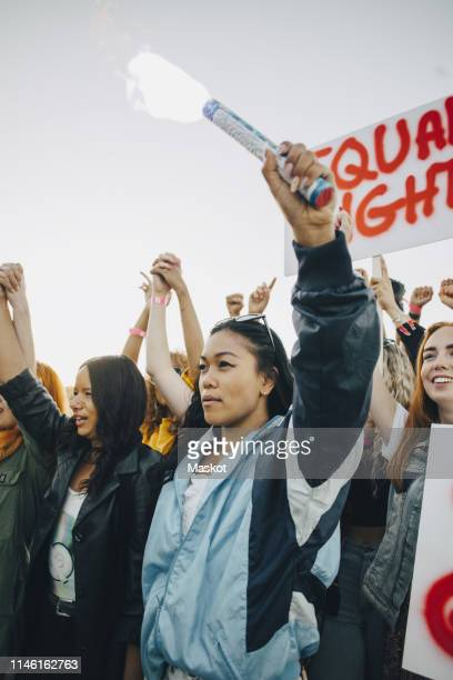 low angle view of women holding hands while protesting for human rights against sky - campaigner stock pictures, royalty-free photos & images
