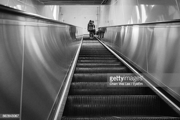 Low Angle View Of Women Moving Up On Escalator
