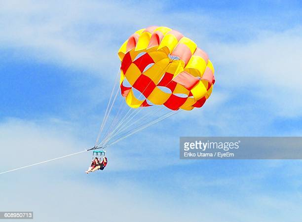 Low Angle View Of Women Parasailing Against Sky