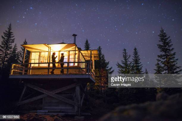 low angle view of women standing in illuminated cottage at night - cottage exterior stock pictures, royalty-free photos & images