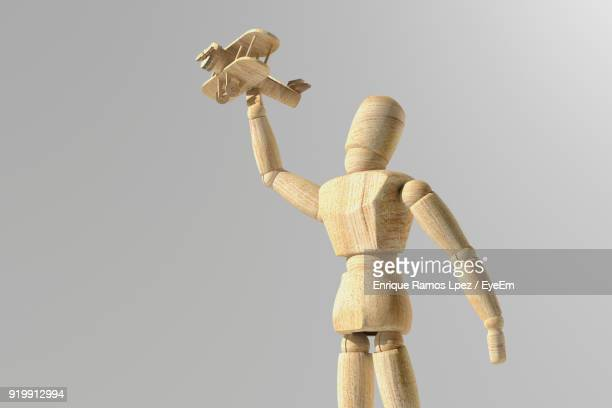 Low Angle View Of Wooden Figurine Against White Background