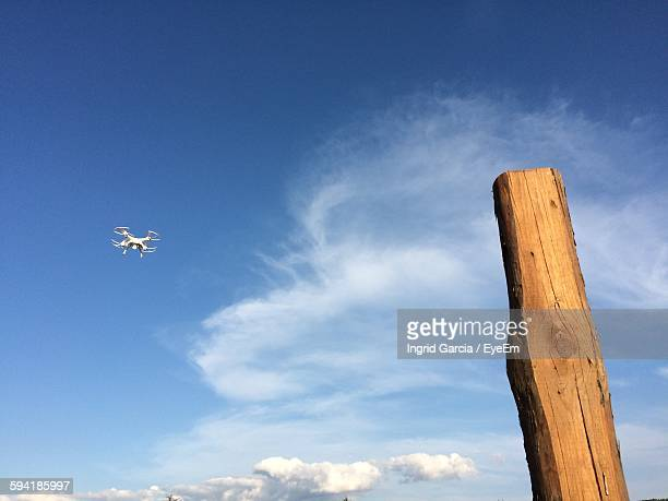 low angle view of wooden post and octocopter against blue sky - オクトコプター ストックフォトと画像