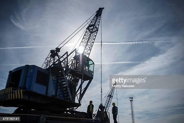 low angle view of workers and crane in silhouette in port - monty rakusen stock pictures, royalty-free photos & images