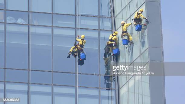 Low Angle View Of Workers Cleaning Modern Office Building
