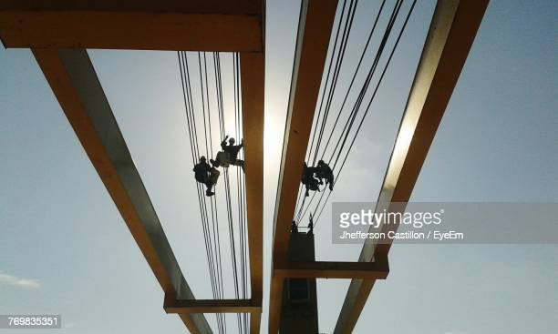 Low Angle View Of Workers On Steel Cable At Bridge Against Sky
