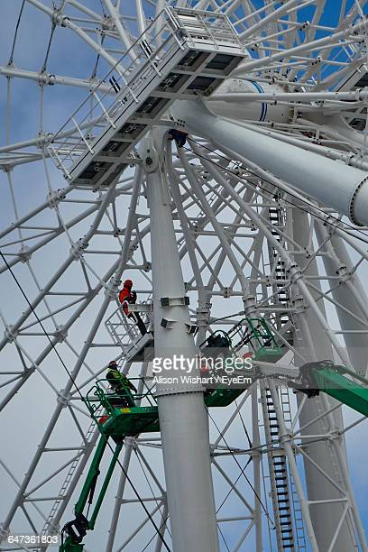 Low Angle View Of Workers Working On Ferris Wheel Against Sky