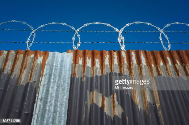 Low angle view of worn corrugated metal fence, razor wire above.