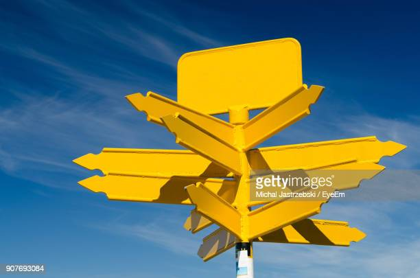 low angle view of yellow arrow symbols against blue sky - guidance stock pictures, royalty-free photos & images