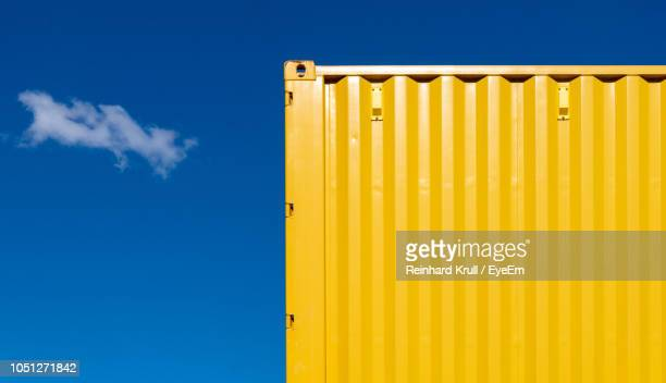 low angle view of yellow cargo container against sky - container stock pictures, royalty-free photos & images