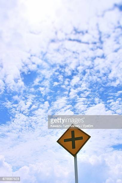 Low Angle View Of Yellow Crossroad Sign Against Sky