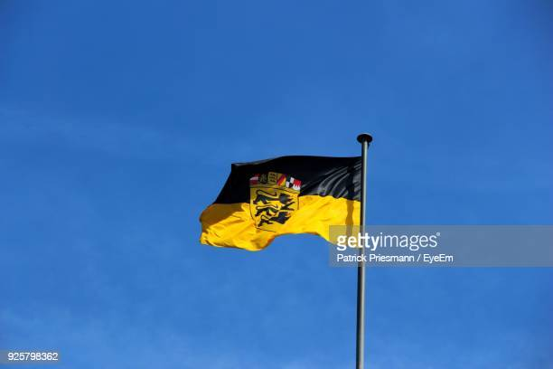 low angle view of yellow flag against blue sky - baden württemberg ストックフォトと画像