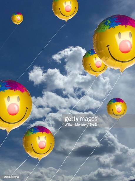 Low Angle View Of Yellow Inflatable Balloon Flying Against Sky