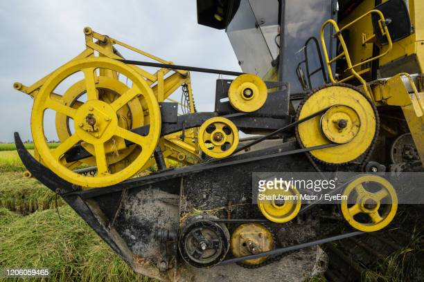 low angle view of yellow machinery on field - shaifulzamri stock pictures, royalty-free photos & images