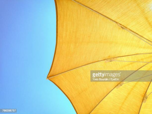 low angle view of yellow parasol against clear blue sky - sombrilla de playa fotografías e imágenes de stock