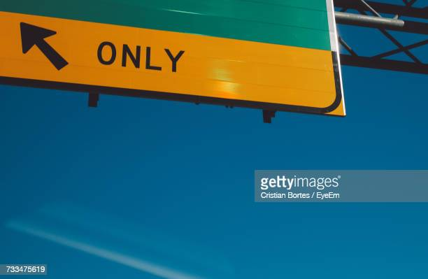 low angle view of yellow road sign against blue sky - bortes stock-fotos und bilder