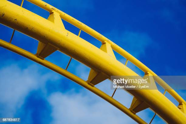 Low Angle View Of Yellow Rollercoaster Against Blue Sky