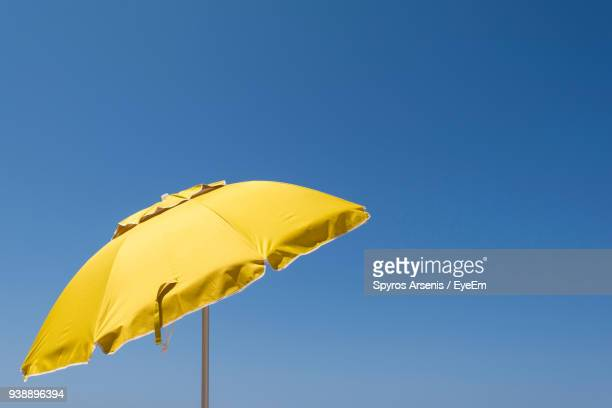 low angle view of yellow umbrella against clear blue sky - sunshade stock pictures, royalty-free photos & images