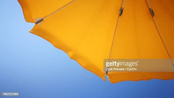 low angle view of yellow umbrella against clear sky - sombrilla de playa fotografías e imágenes de stock