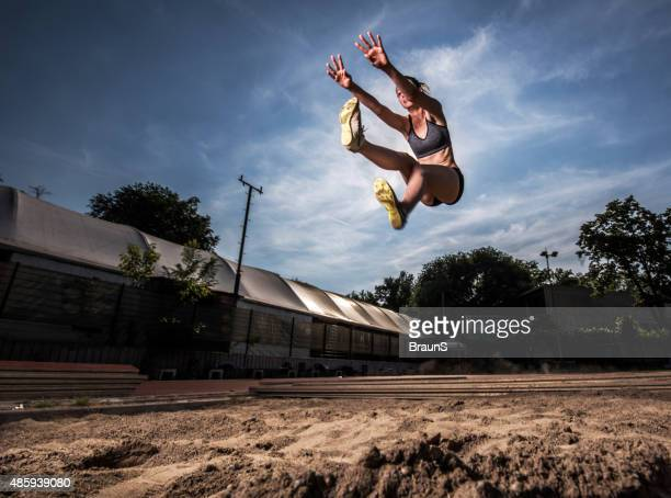 Low angle view of young athletic woman in long jump.